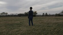 A Teen Boy Stands In A Kansas Field By Himself Watching The Sun Setting. The Teenager Is Wearing Jeans And A Hoodie Shirt And Has Dark Hair.