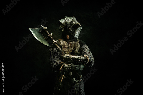 Portrait of a medieval fighter in armor, in profile, arms crossed, ax in his han Wallpaper Mural