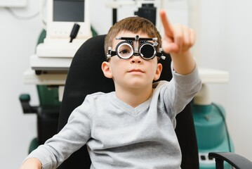 Small serious boy sitting on chair office of vision test. doctor picks up lenses to special glasses