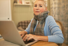 Portrait Of Sick Mature Woman Employee Has To Do Working Tasks On Medical Leave Sitting At Home Office Using Portable Computer For Remote Work Staring At Camera With Hopeless Look On Her Face