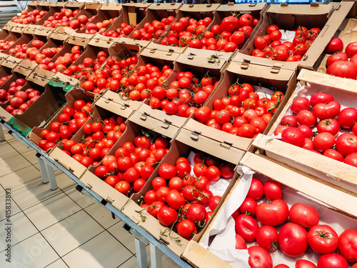 Tomatoes are in boxes in the supermarket