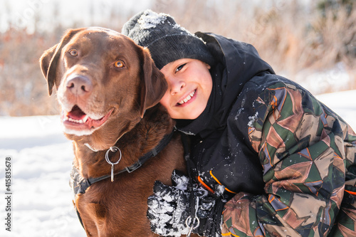 Portrait of little boy with labrador dog in winter season Fotobehang