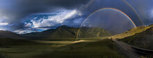 Panoramic View Of Colorful Rainbows Over Road Between Green Hills