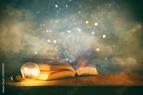 Fototapeta Magical image of open antique book over wooden table with glitter overlay obraz