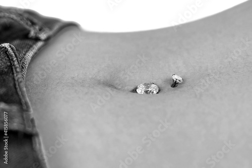 Belly button or navel piercing, of young woman wearing jeans isolated on white. Close-up macro shot. Dramatic monochrome, black and white photo. High quality image.