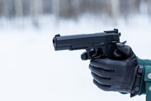 Gun In Hand Close-up. Black Leather Gloves With A Pistol. Shooting In Nature.