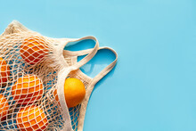 Mesh White Cotton Reusable Bag With Oranges On A Blue Background. Environmentally Friendly Shopping, The Environment And The Concept Of Healthy Foods, Citrus Fruits With Vitamin C. Place For Text