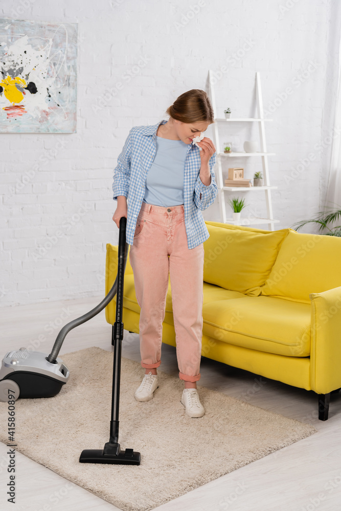 Fototapeta Woman with allergy on dust cleaning carpet with vacuum cleaner