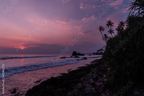 Obraz Pomarańczowo fioletowe niebo z zachodzącym słońcem, tropikalny krajobraz wybrzeże z oceanem. - fototapety do salonu