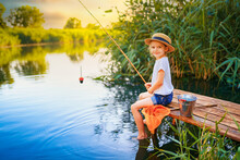 Little Boy In Straw Hat Sitting On The Edge Of A Wooden Dock And Fishing In Lake At Sunset.