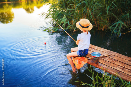 Fotografia Little boy in straw hat sitting on the edge of a wooden dock and fishing in lake at sunset
