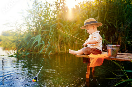 Fotografija Little boy in straw hat sitting on the edge of a wooden dock and fishing in lake at sunset