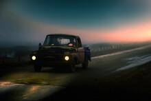 Antigua Pickup Deteriorada Circula Por Un Camino De Tierra, En Un Clima Nublado Y Brumoso, Con Dos Personas En Su Interior, Mientras Cae El Sol