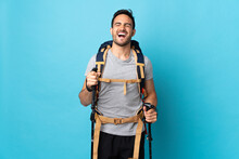 Young Caucasian Man With Backpack And Trekking Poles Isolated On Blue Background Laughing
