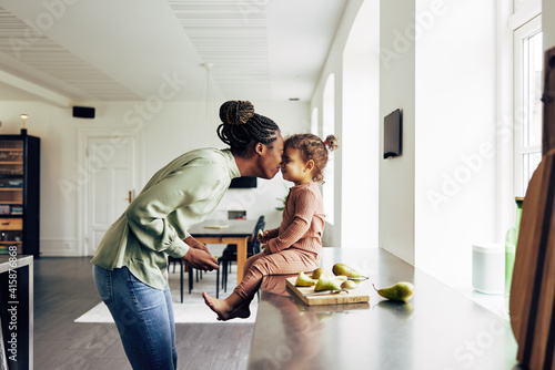 Fotografia Loving mom and her little girl having a snack at home