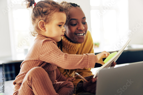 Stampa su Tela Smiling mom working from home and looking after her daughter