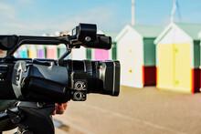 En Foco Y En Primer Plano Una Cámara De Video Profesional. Fuera De Foco Coloridas Casetas En El Paseo Marítimo De La Playa De Brighton, Reino Unido