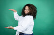 canvas print picture - Young african american girl wearing white shirt over green background gesturing with hands showing big and large size sign, measure symbol. Smiling . Measuring concept.