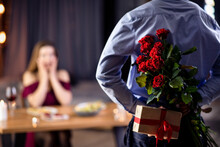 Romantic Black Guy Holding Flowers And Gift Behind Back, Surprising His Girlfriend