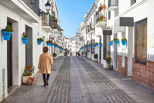 Obraz na plátně Lady walking a little dog in picturesque Mijas street with flower pots on facades