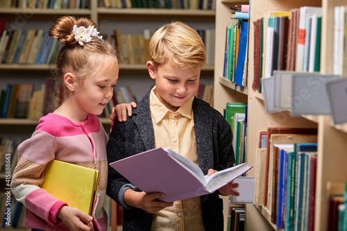 Fotografia, Obraz boy and girl reading book in school library, people lifestyles and friend Education and friendship concept