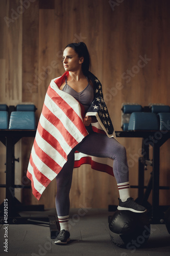 Fototapeta American patriot girl with an athletic physique posing on a wooden wall backgrou