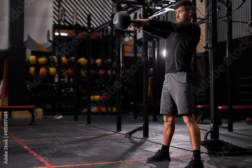 Vászonkép fit muscular man with big muscles holding heavy kettlebell for cross fit swing training hard core workout in the gym, alone, wearing sportive clothes