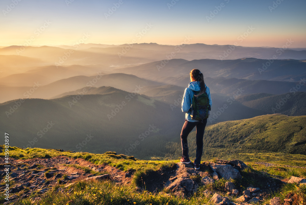Fototapeta Girl on mountain peak with green grass looking at beautiful mountain valley in fog at sunset in summer. Landscape with sporty young woman, foggy hills, forest, sky. Travel and tourism. Hiking