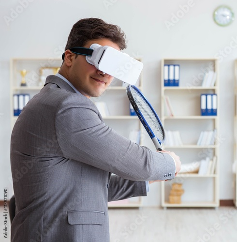 Fototapeta Businessman playing virtual reality tennis in office with VR gog obraz