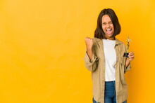 Young Hispanic Woman Holding An Award Statuette Raising Fist After A Victory, Winner Concept.