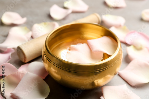 Fototapeta Golden singing bowl with petals on grey table, closeup. Sound healing obraz