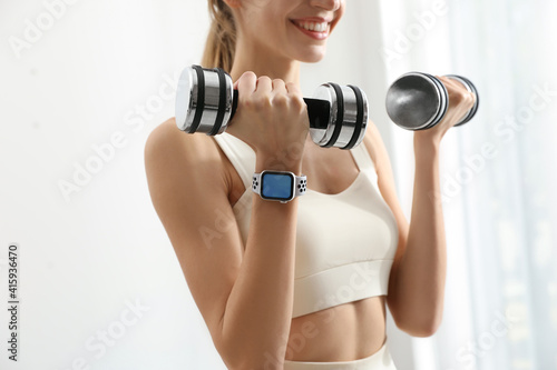 Fototapeta Young woman wearing smart watch during training indoors, closeup obraz