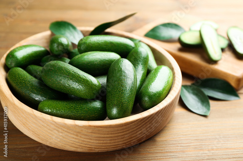 Fototapeta Fresh seedless avocados with green leaves in bowl on wooden table, closeup obraz