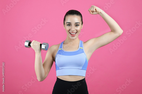 Fototapeta Woman with dumbbell as girl power symbol on pink background. 8 March concept obraz