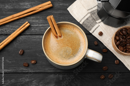 Fototapeta Cup of hot coffee with aromatic cinnamon on black wooden table, flat lay obraz