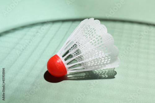Fototapeta Plastic shuttlecock and shadow of racquet on light background, closeup. Badminton equipment obraz