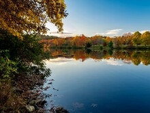 Keystone Lake In Keystone State Park In West Moreland County In The Laurel Highlands Of Pennsylvania In The Fall Right Before Sunset With The Fall Foliage And Trees Reflecting In The Water.