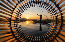 Traditional Thai Fisherman. Asian Fisherman On A Wooden Boat Thai Traditional Fishermen Catch Water Fish In The Natural River. Fisherman At The Sunset Time.