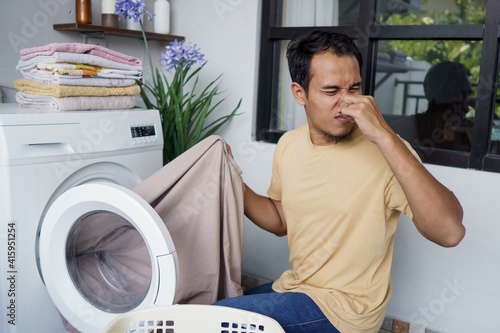 Fototapeta Housework. asian Man doing laundry at home loading clothes into washing machine bad odor. smell badly obraz