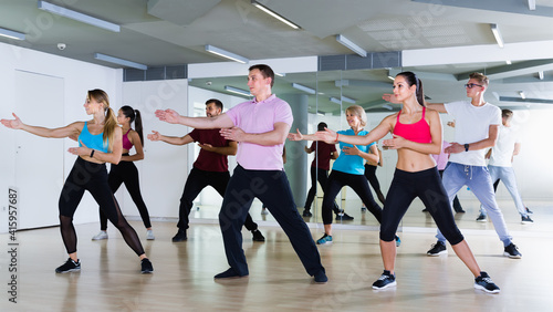 Photo glad men and ladies dancing aerobics at lesson in the dance class