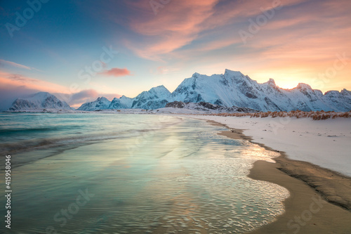 Fototapeta Winter sunset over the sea and mountains, colorful northern sunrise and sunlight in pink clouds