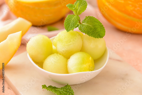 Bowl with sweet melon balls on color background
