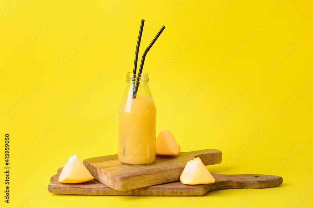 Fototapeta Bottle with melon smoothie on color background