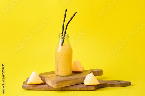 Fototapeta Bottle with melon smoothie on color background obraz