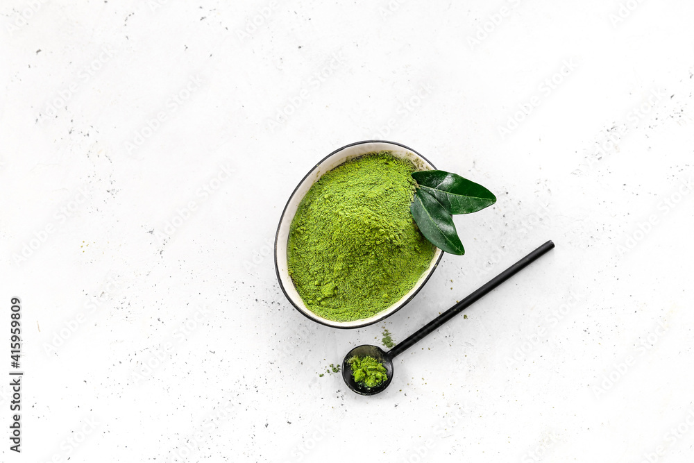 Fototapeta Bowl with powdered matcha tea and scoop on light background