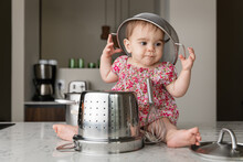Funny Baby Playing With Kitchen Utensils Wearing Colander On Head