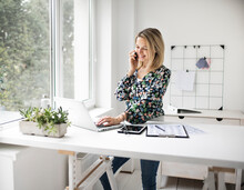 Businesswoman Telephoning Customer Using Cellphone While Working At Ergonomic Standing Desk In Office.