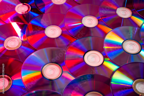Background CD and DVD discs laid out on a flat surface. Background for saving information. Abstraction. #415983469