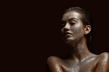 Glittering silver female body art, young beautiful naked girl with wet hair, skin in sparkles, copy space