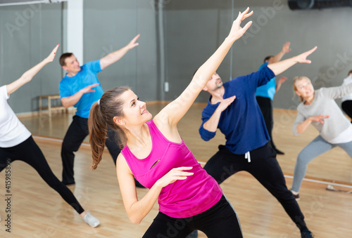Foto Cheerful young woman enjoying active dances in modern dance studio